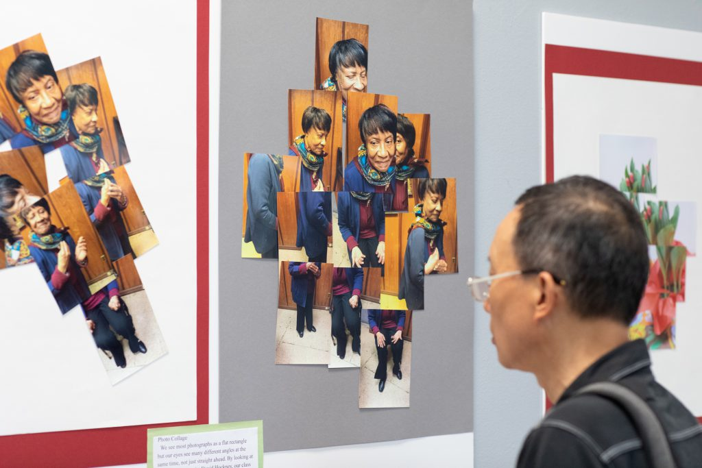 A photo of a man looking at an exhibit of photo collage artwork.