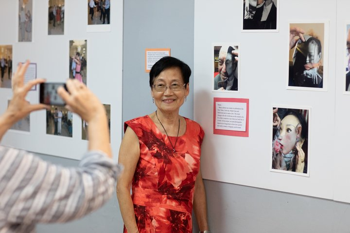 A photo of a woman standing in front of her photographer work. Another person is taking the artist's photo.