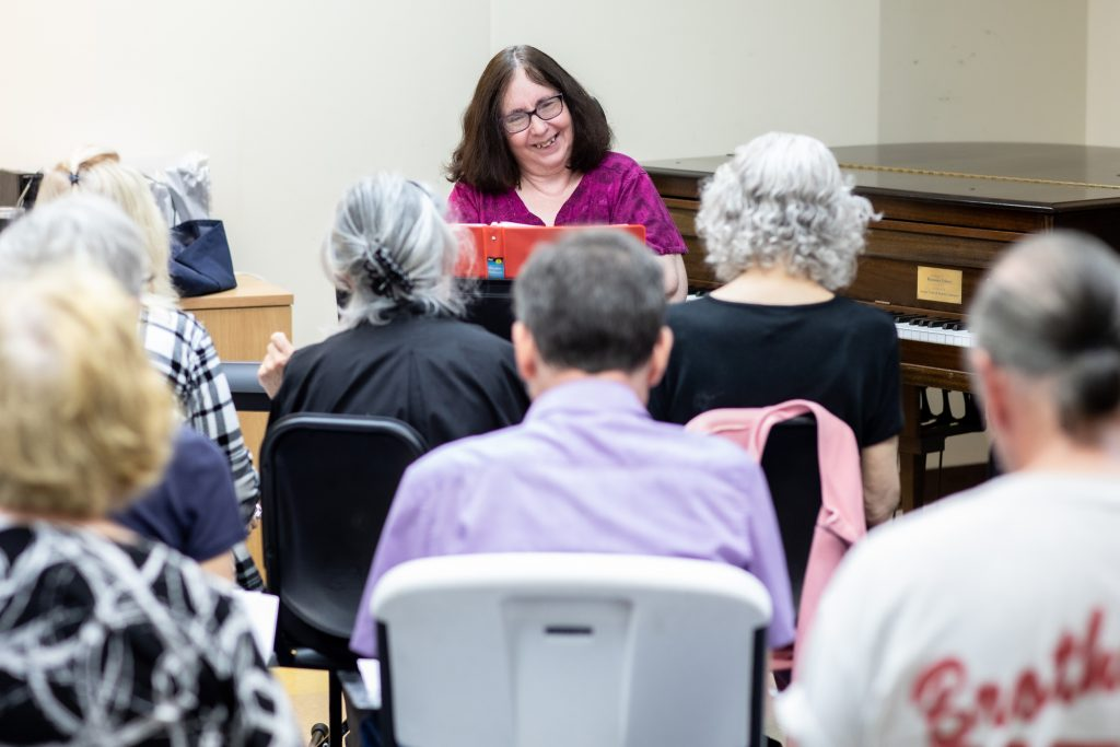 A photo of a choir group, seated, in front of teaching artist, who is sitting at a piano.