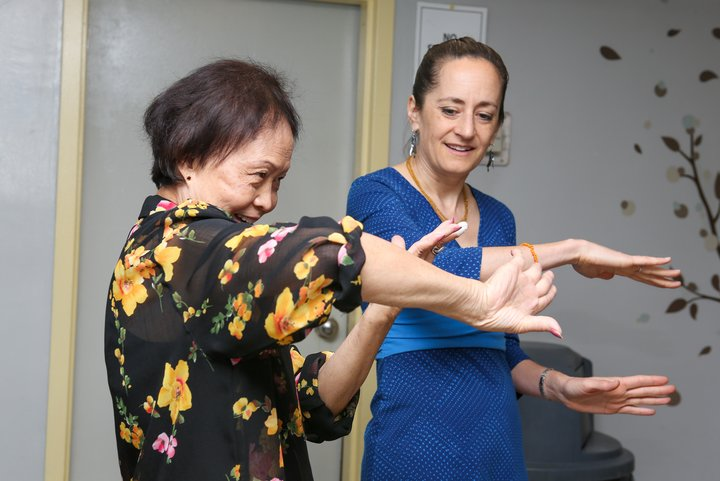 This photo shows two women, one is teaching the other to dance, and is demonstrating a complex arm movement.